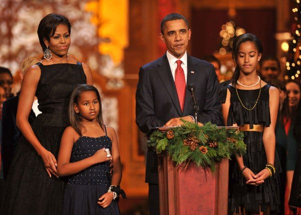 President Barack Obama speaks onstage as Michelle Obama, Sasha Obama and Malia Obama look on during TNT's 'Christmas in Washington 2010' at the National Building Museum on December 12, 2010 in Washington, DC.
