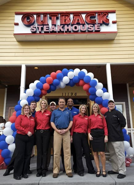 Employees of Outback Steakhouse pose with Lifetime TV's Brian McNamara as he hosted a special lunch for Army wives during the 'Thanks For Giving' event at Outback Steakhouse on January 30, 2011 in Savannah, Georgia.