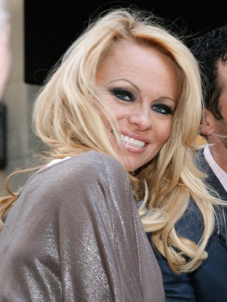 Pamela Anderson and Tony Dovolani attend the Horse-drawn Carriage Industry protest on the streets of Manhattan on April 30, 2011 in New York City.