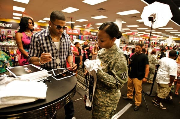 Rapper Nelly signs autographs for a member of the U.S. Army 3rd Infantry Division during the Apple Bottoms by Nelly & CitiTrends in-store event on June 22, 2011 in Savannah, Georgia.