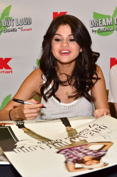 Selena Gomez signs posters for fans at an in-store appearance at Kmart's Philadelphia Market Street Store during the launch of her new clothing line on August 19, 2011 in Philadelphia, Pennsylvania.