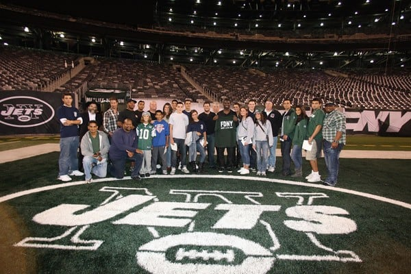 Running Back LaDainian Tomlinson of the New York Jets poses with the participants of NY Jet LaDaninian Tomlinson's 911 Event & Unveiling Of Bermano Artwork at MetLife Stadium on September 11, 2011 in East Rutherford, New Jersey.