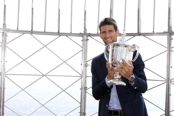 US Open Champion, Novak Djokovic of Serbia, poses with the championship trophy as he visits The Empire State Building on September 13, 2011 in New York City.
