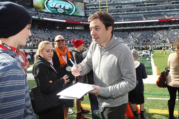 Jimmy Fallon signs an autograph for a fan when he attends the San Diego Chargers vs New York Jets game at MetLife Stadium on October 23, 2011 in East Rutherford, New Jersey.