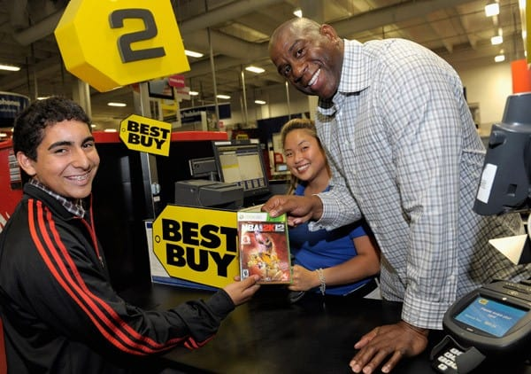NBA legend Earvin 'Magic' Johnson and a Best Buy employee make the first sale during the NBA 2K12 Launch Event at the Best Buy in West LA on October 3, 2011 in Los Angeles, California.