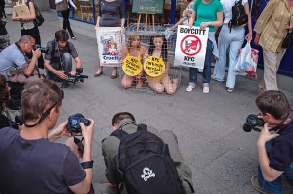 Animal activists Jodi Ruckley (left) and Karolina Kostrzzewa-Colwill (right) in a cage during a protest for PETA's Campaign Against KFC in front of a KFC restaurant in Warsaw, Poland.